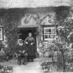 Photo of old couple sitting outside Bay Tree Cottage Breinton Common early 1900s